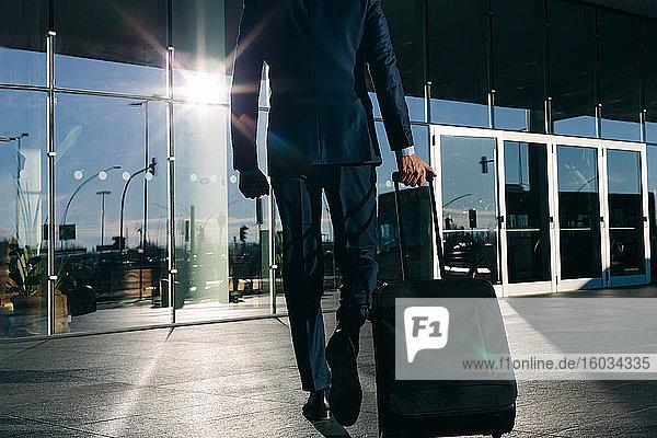 Geschäftsmann mit Rollgepäck fährt an Glasgebäude vorbei  Malpensa  Mailand