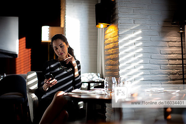 Sophisticated young woman reading smartphone texts in boutique hotel restaurant  Italy