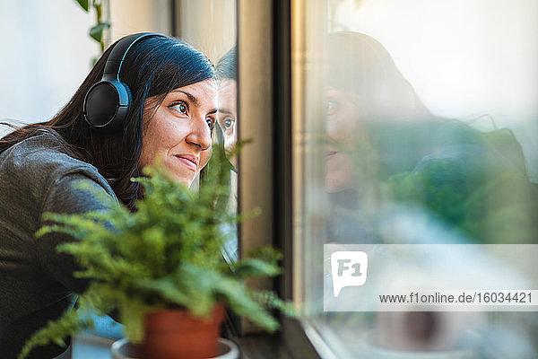 Frau mit Kopfhörern  die während der Corona-Virus-Krise durch ein Fenster schaute.