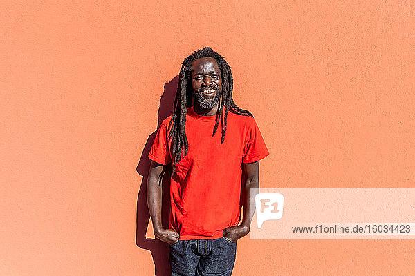 Porträt eines schwarzen Mannes mit Dreadlocks  der vor einer orangefarbenen Wand steht und in die Kamera lächelt.