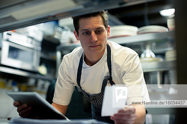 Junger männlicher Koch benutzt digitales Tablett und liest die Essensbestellung in der Küche