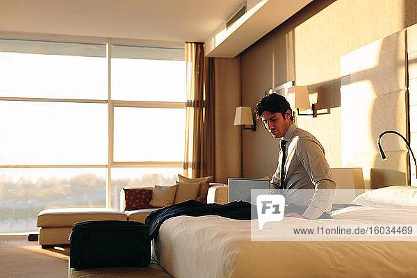 Geschäftsmann mit Laptop auf dem Bett eines Hotelzimmers