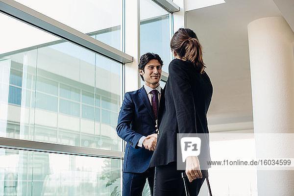 Geschäftsmann und Geschäftsfrau mit Rollgepäck im Hotelgebäude