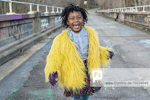 Portrait happy girl in yellow fuzzy jacket on bridge