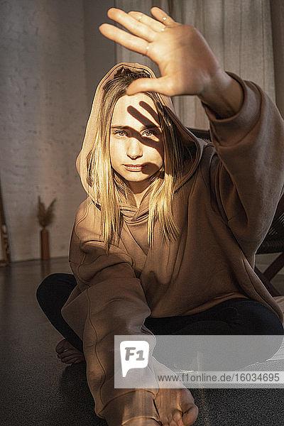 Porträt einer selbstbewussten jungen Frau mit Kapuzen-Sweatshirt  das die Sonne mit der Hand abhält