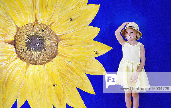 Portrait cheerful girl in yellow dress against painted sunflower backdrop