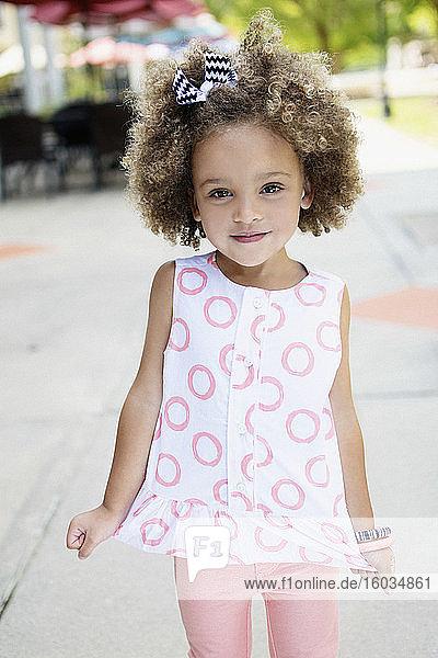 Porträt eines süßen Mädchens in rosa-weißem Hemd auf dem Bürgersteig