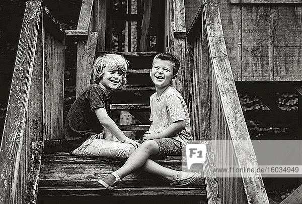 Portrait happy brothers sitting on cabin steps