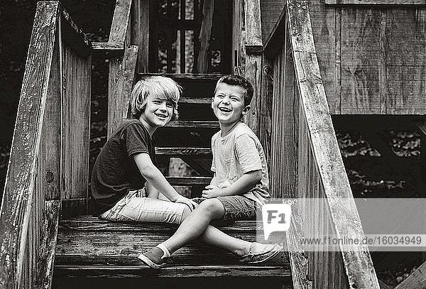 Portrait glückliche Brüder auf Kabinentreppe sitzend