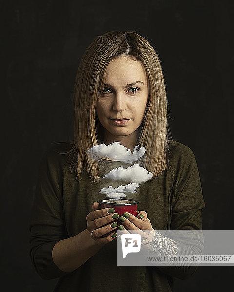 Portraitfrau hält Kaffeetasse mit Wolken