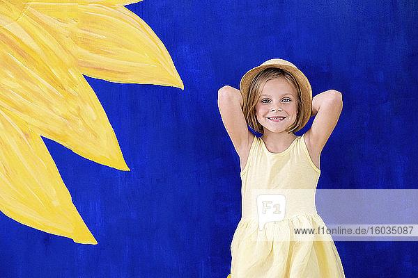 Porträt eines lächelnden Mädchens in gelbem Kleid vor lebhaftem Hintergrund