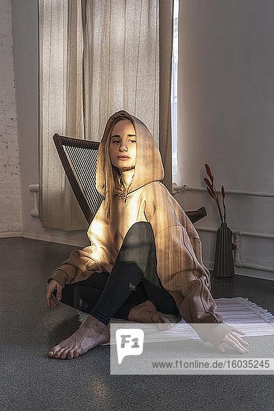 Porträt einer selbstbewussten jungen Frau mit Kapuzensweatshirt im Yoga-Studio