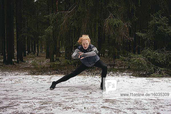 Athletische Läuferin streckt sich in verschneiten Wäldern