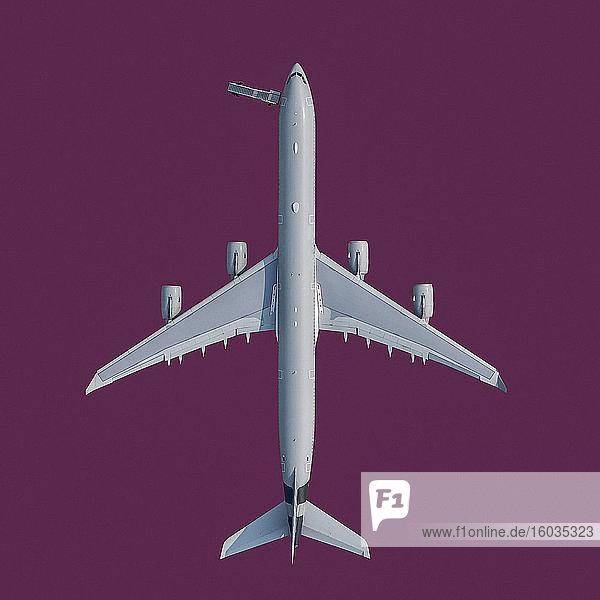 Blick von oben Flugzeug auf violettem Hintergrund