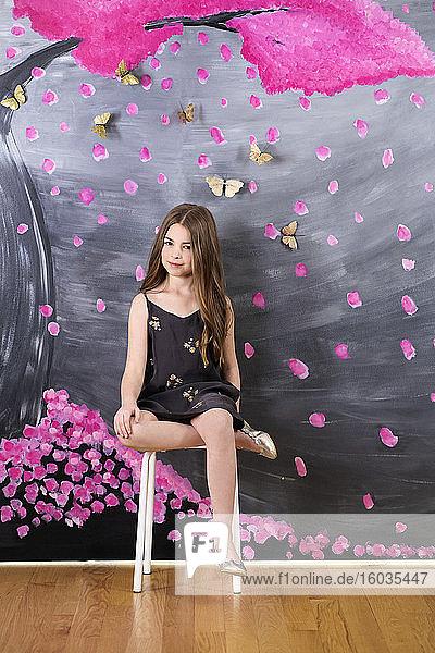Portraitmädchen in Kleid an der Wand sitzend  bemalt mit rosa Baum und Schmetterlingen
