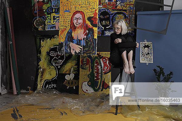Barfüßige junge Künstlerin im Atelier mit Gemälden