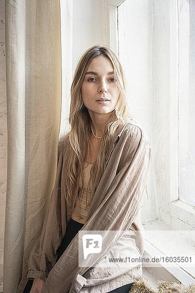 Porträt selbstbewusste  schöne junge blonde Frau im Fenster