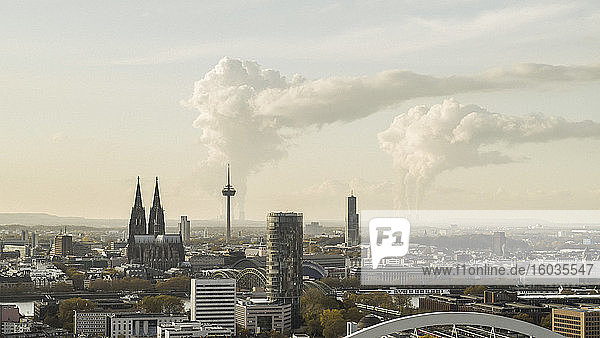 Smoke rising from factories behind Cologne cityscape  Germany