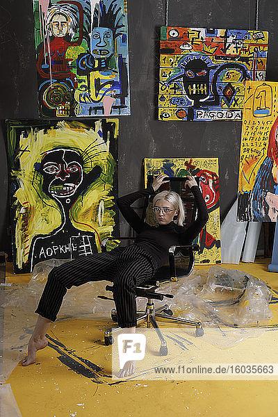 Porträt selbstbewusste  kühle junge Künstlerin im Atelier mit Gemälden