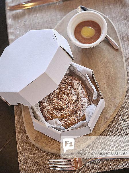 Ensaimada mit Puderzucker in Papierbox auf Holztisch