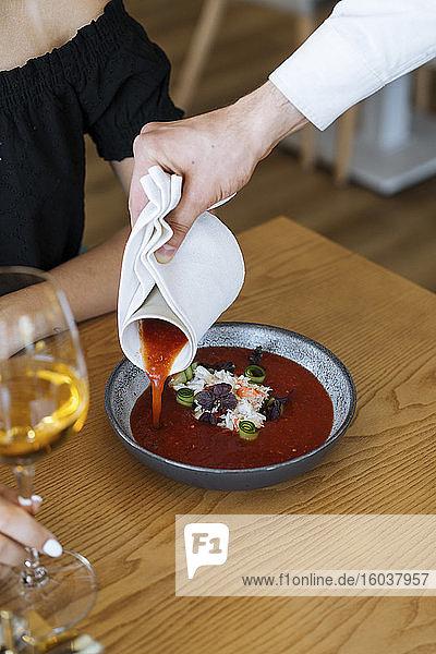 Kellner gießt Tomatensauce auf Königskrabbenfleisch mit Gurke  Basilikum und Olivenöl