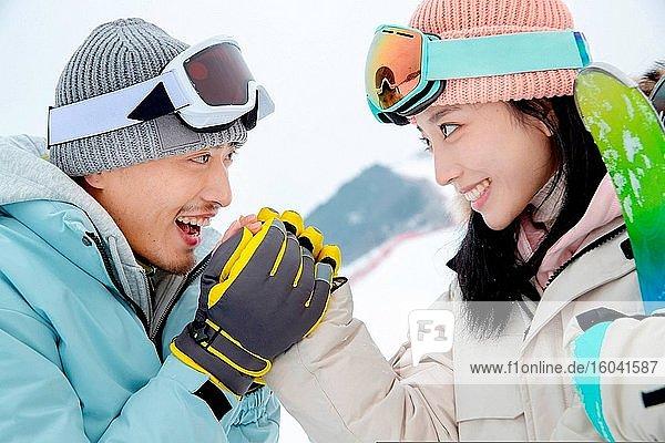 Ski junger Mann zu seiner Freundin über Ihre Hand