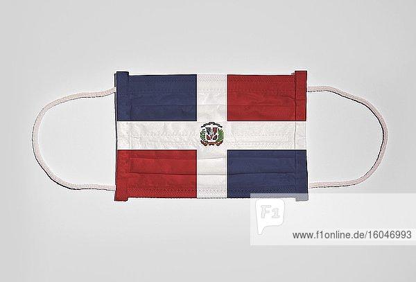 Symbolbild Corona-Krise  Mundschutz  Atemschutzmaske  Mund-Nase-Schutz mit Flagge von Dominikanische Republik  weißer Hintergrund