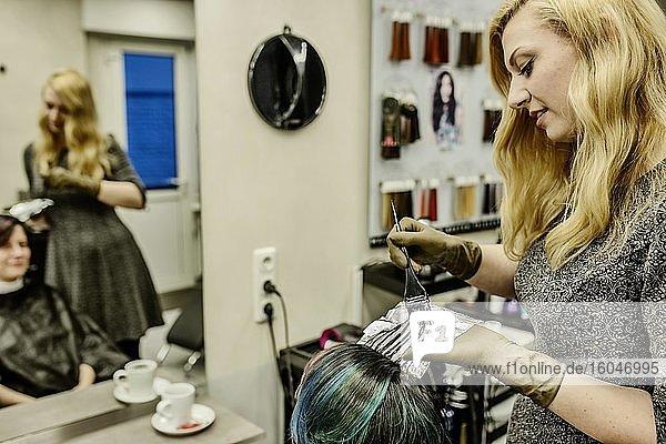 Friseurin in eimem Friseursalon färbt Kundin Haarsträhnen mit Alufolie  Köln  Nordrhein-Westfalen  Deutschland  Europa