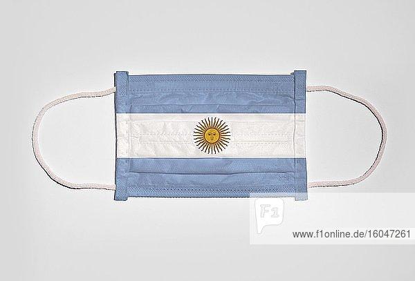 Symbolbild Corona-Krise  Mundschutz  Atemschutzmaske  Mund-Nase-Schutz mit Flagge von Argentinien  weißer Hintergrund