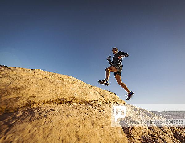 USA  Utah  St. George  Mann springt beim Laufen in felsiger Landschaft