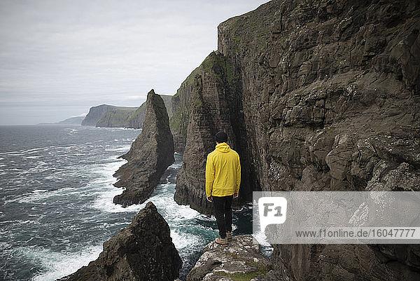 Dänemark  Färöer-Inseln  Sorvagur  Mann schaut auf Meeresküste mit Klippen