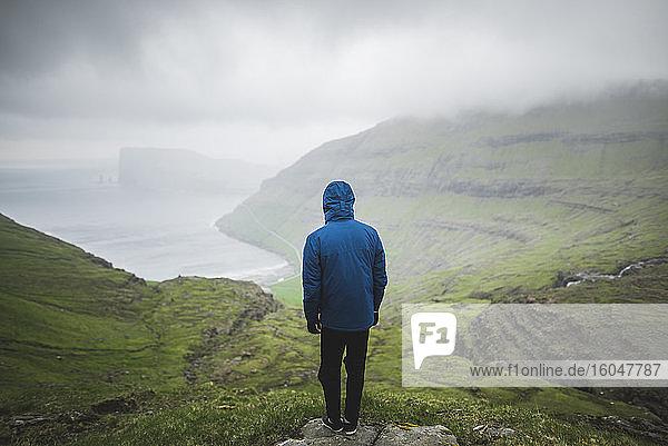 Dänemark  Mann steht auf einer Klippe über dem Meer und schaut auf die Aussicht