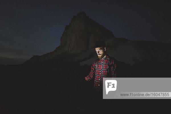 Ukraine  Krim  Mann mit Hut mit leuchtendem Telefon  der nachts in der Nähe des Weißen Berges steht