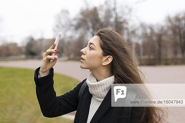 Russland  Tscheljabinsk  Junge Frau schaut auf Smartphone