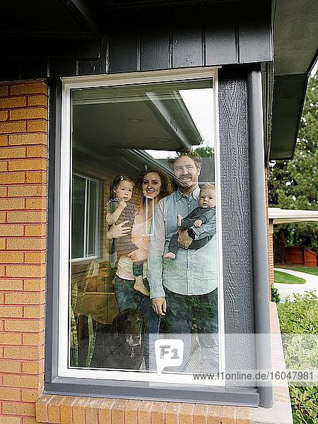 Familie mit Kindern (6-11 Monate  2-3) beim Blick durchs Fenster