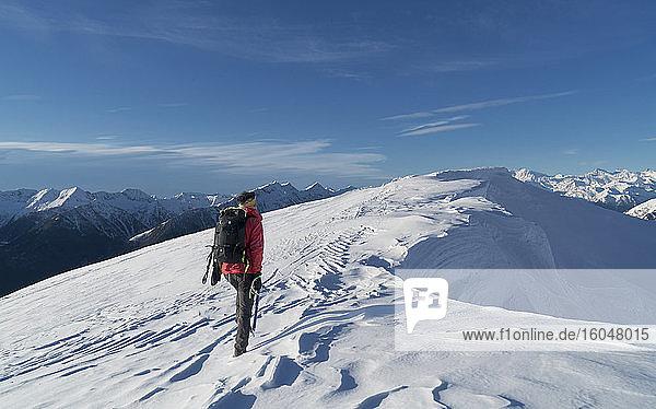 Italien  Piemont  Alpen  Monte Rosa  Bergsteiger erreicht schneebedeckten Berggipfel