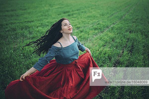 Junge Frau tanzt auf dem Feld