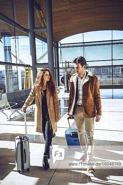 Geschäftspaar im Gespräch  während es mit Gepäck im Abflugbereich des Flughafens spazieren geht