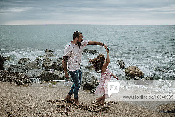 Daughter dancing with father at beach