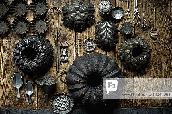 Sammlung alter rustikaler Kochutensilien  darunter Backformen  Servierschaufeln  Reiben  Schneebesen und Trichter Sammlung alter rustikaler Kochutensilien, darunter Backformen, Servierschaufeln, Reiben, Schneebesen und Trichter