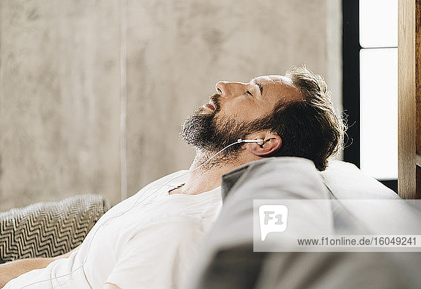 Mature man sitting on couch  relaxing  listening music with earphones