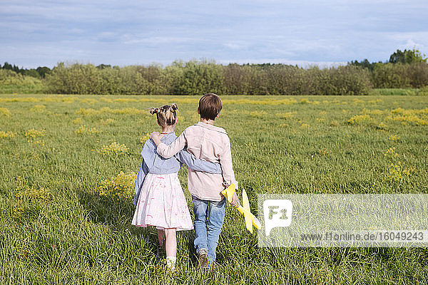Boy holding toy airplane while standing with arm around sister on rape field