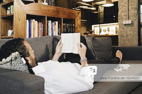 Mature man lying on couch  relaxing  reading book