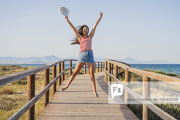 Excited teenage girl jumping on boardwalk at beach against clear sky
