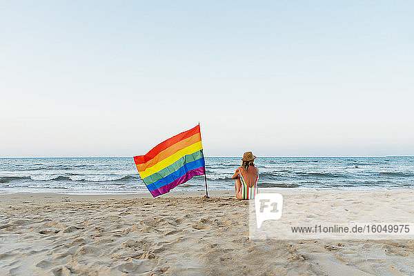 Marure woman sitting on the beach with gay pride flag