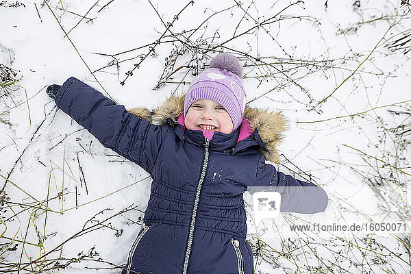 Happy girl lying with arms outstretched in snow