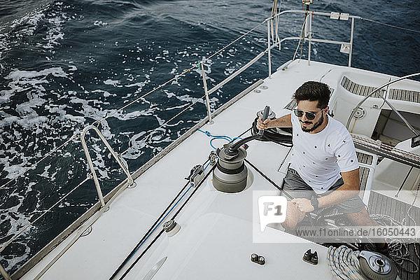 Junger Segler mit Sonnenbrille beim Manövrieren mit einer Winde im Segelboot Junger Segler mit Sonnenbrille beim Manövrieren mit einer Winde im Segelboot