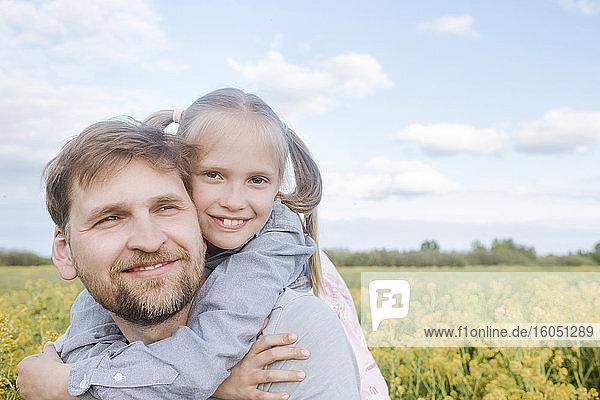 Smiling man giving daughter piggyback against sky