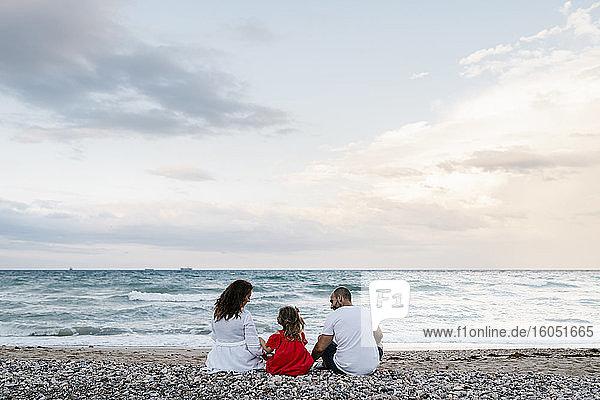Familie verbringt Zeit am Strand bei bewölktem Himmel
