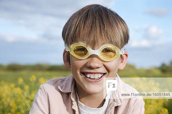 Blond boy wearing swimming goggles at rape field on sunny day